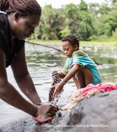 A woman and a girl washing clothes by the side of a lake. Credit Marcus Perkins/Merck KGaA