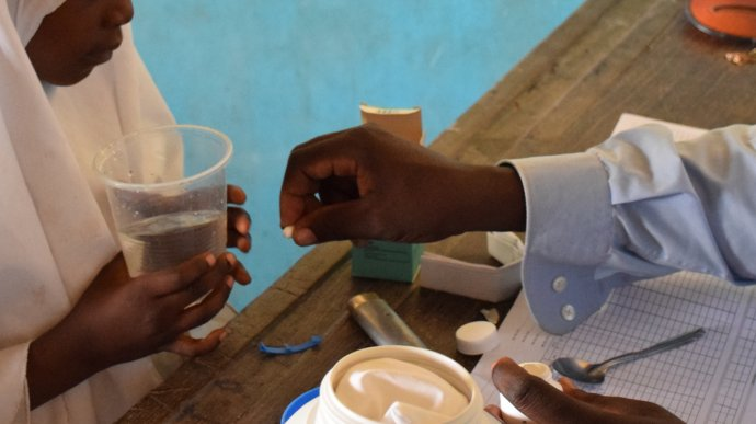 Deworming tablets being handed to a pupil. Image copyright Schistosomiasis Control Initiative