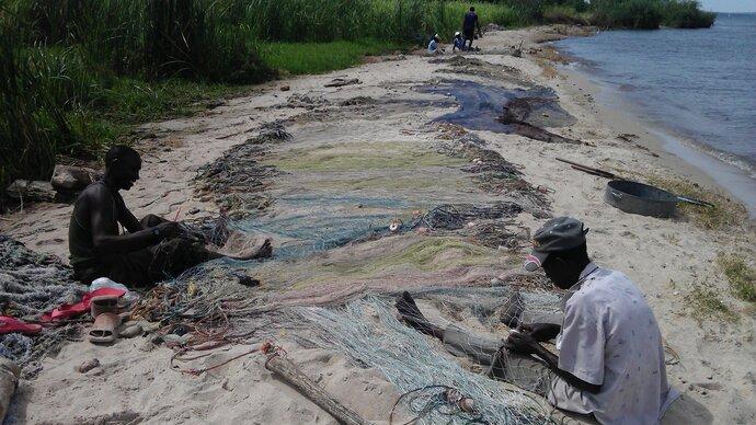 Fishermen mending nets next to a lake. Image copyright Anouk Gouvras