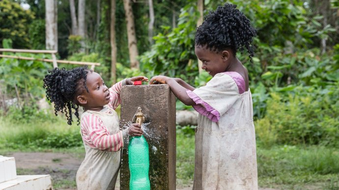 Two children filling a bottle of water from a tap