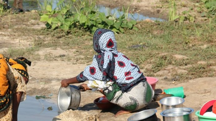 Woman washing pots in local water body - Zanzibar transmission site. Image credit David Rollinson