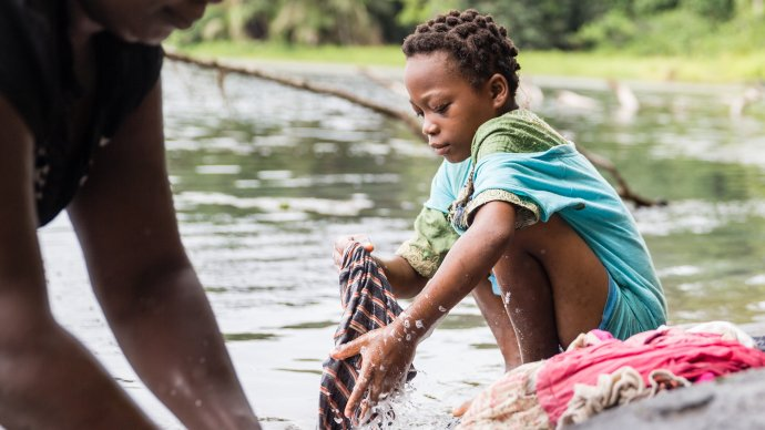 Young person washing clothes in water. cr. M Perkins