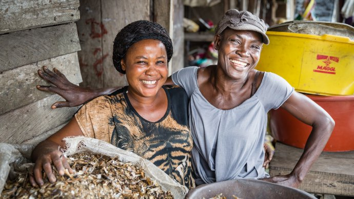 Photo of two women smiling and working in a market