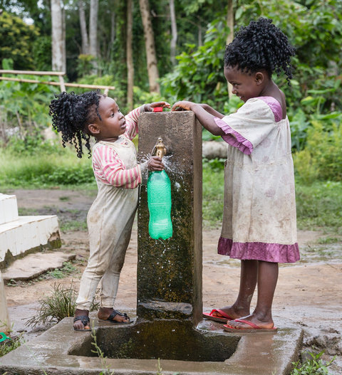 Two children collecting water from a tap
