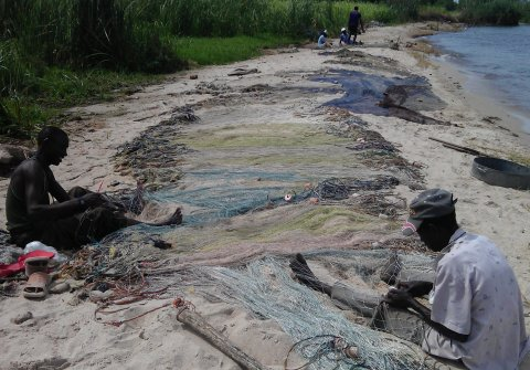 Fishermen mending nets next to a lake. Copyright Anouk Gouvras