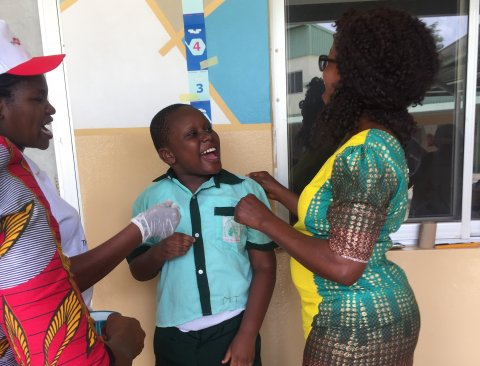 Older boy feels supported by trusted adults during deworming MDA at school for children with disabilities in Bwari Area Council, FCT, Nigeria © CBM 2019