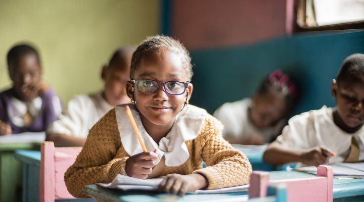 Little girl looks up from her desk at school
