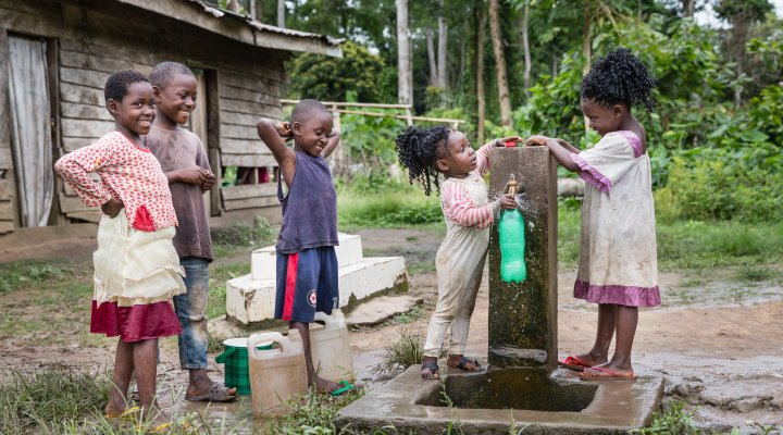Five children of different ages collecting water into bottles from a tapped water pump