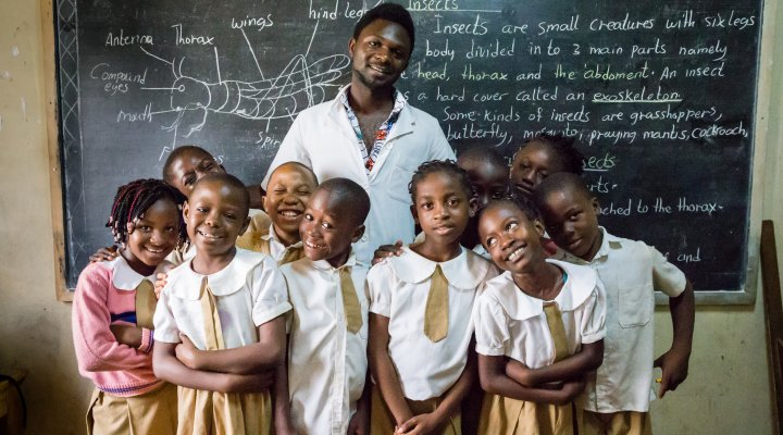 Smiling, a teacher and his pupils stand infront of a blackboard which they have been studying.