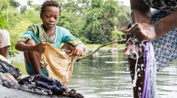 A child washes clothes by the river